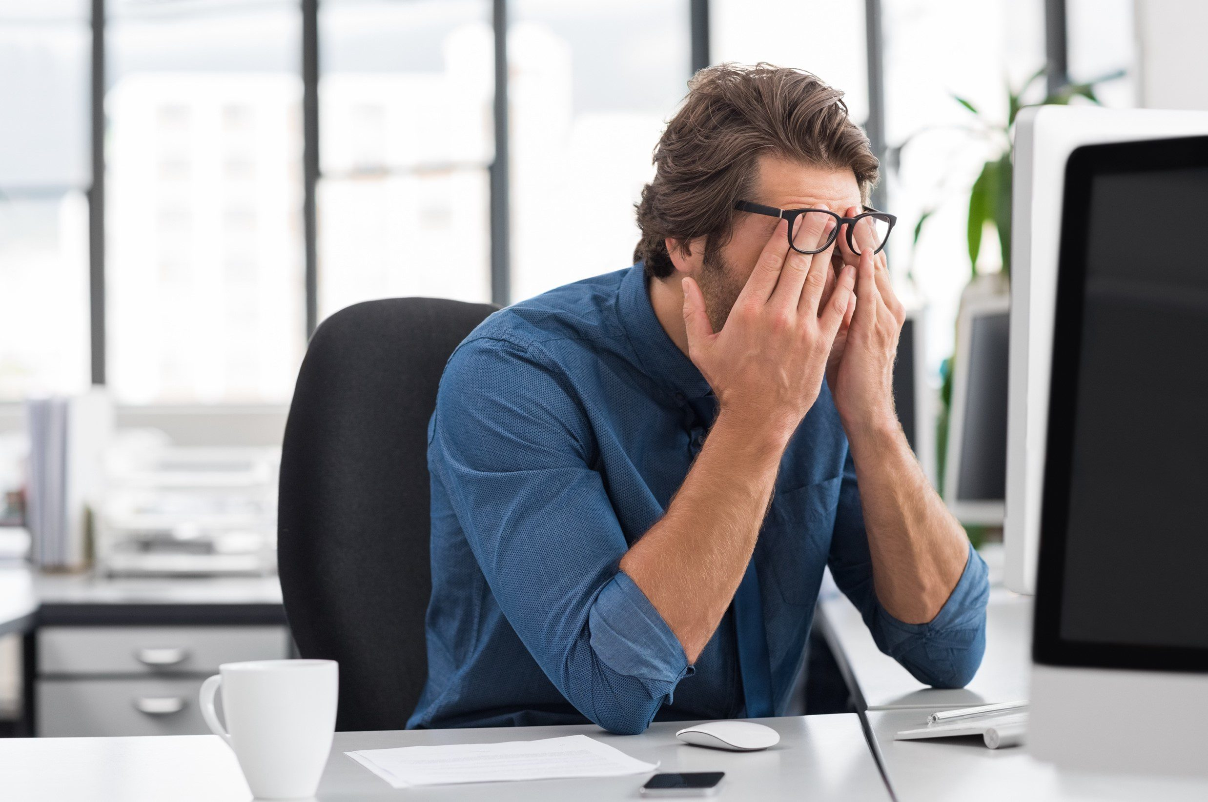 Man with glasses at office desk rubbing his eyes in front of a computer screen